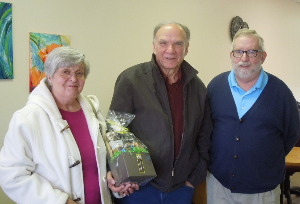 Dave and Debbie Clonch hold a gift from the New River Valley Disability Resource Center's Frank Hayes, Executive Director