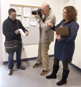 A woman with reddish brown hair speaks to a reporter, a dark haired man looking at a small notepad and writing notes, and a photographer, a tall gray haired man holding a camera to his eye