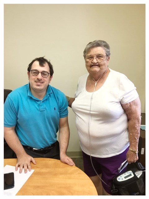 On the left stands Matt Shelor, a 36 year old white make standing roughly 5 feet tall with dark hair and dark framed glasses. On the right stands Ms. Farley, who is an older white female with gray short hair and glasses standing next to Matt. She is wearing a white short-sleeve blouse and purple shorts, is wearing an oxygen cannula and is holding a portable oxygen machine in her left hand. Both of them are smiling at the camera as they stand behind Matt's desk in his office.