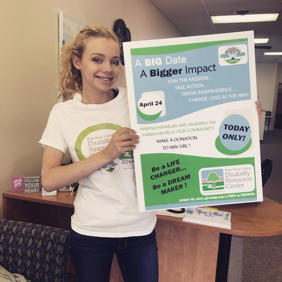 A teenage girl with blond curly hair stands smiling and holding a large sign that highlights the Give Big fundraising event for that day