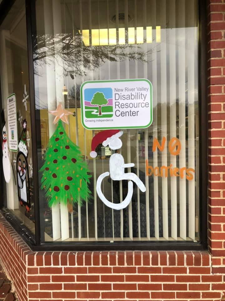 "a Christmas tree standing beside a disabled placard symbol wearing a Santa hat with the words ""No Barriers"" written beside it"