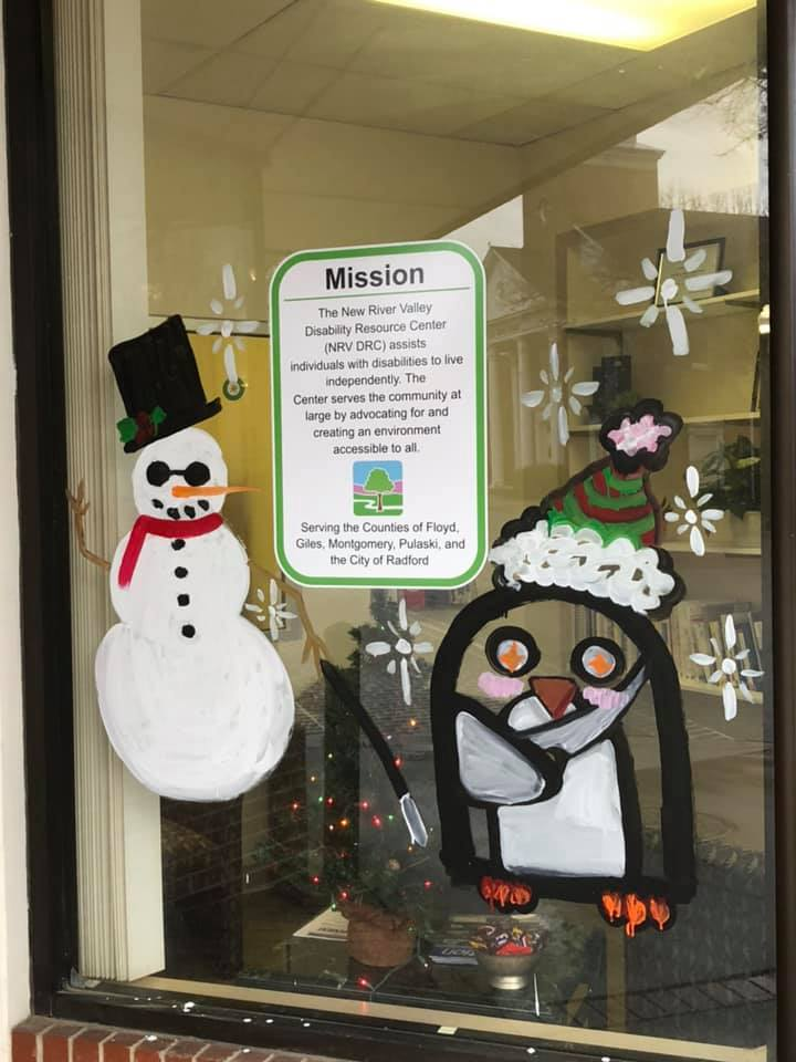 Painted on NRV DRC's windows bA blind snowman with tinted glasses and a long cane and a penguin with it's arm in a sling
