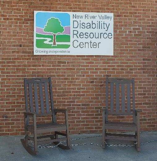 """This picture contains part of the outside of NRV DRC's office building. Pictured are 2 brown rocking chairs with NRV DRC's sign located  in between them mounted on a brick  building. It has a white background with the the NRV DRC logo which contains a cartoon style image of a tree with a brown trunk and a full green top of leaves. It is growing from a green grassy area. Behind it is a small stream that is represented by a white line that curves. Above the grass is a lilac mountain and above that is a blue sky. Below the image reads, """"Growing independence."""" in grey writing. Beside the logo reads, """"New River Valley Disability Resource Center"""" in grey writing."""